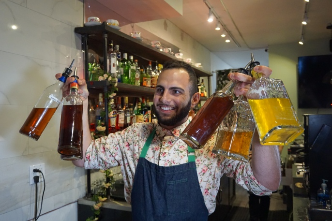 Bartender holding bottles of spirits