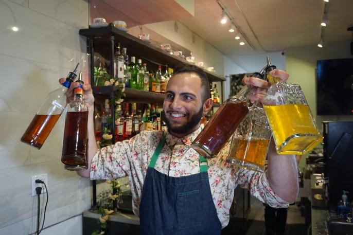 Bartender holding bottles of spirits